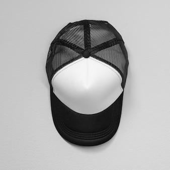 Białe czapki z czarnymi sieciami na tle cementu. widok z góry na czapkę baseballową.