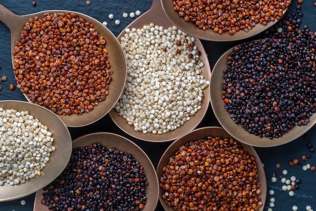 Białe, czerwone i czarne nasiona komosy ryżowej w łyżkę i na tle, bliska, widok z góry