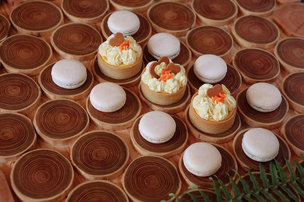 Białe, delikatne, skromne makaroniki na drewnianym tle, pastelowy odcień kremu wewnątrz francuskich ciasteczek