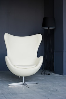 Białe designerskie krzesło we wnętrzu czarnego loftu studio