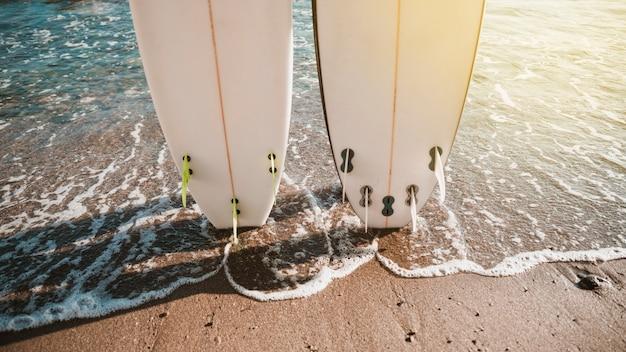 Białe deski surfingowe na wybrzeżu w pobliżu wody