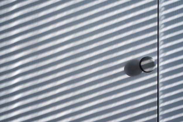 Białe drewniane drzwi szafy z cieniem od żaluzji. słoneczny dzień, wnętrze bakground