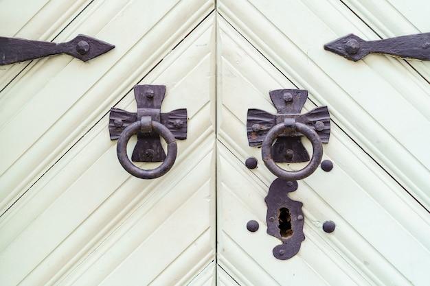 Białe drewniane drzwi z zamkiem i czarnymi metalowymi okuciami.