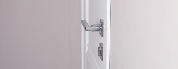 Białe drewniane drzwi z żelazną klamką