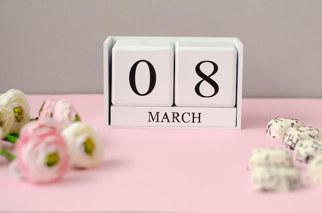 Białe drewniane kostki z 8 marca, ciasteczka w kształcie serca i kwiaty na pastelowym różowym tle.