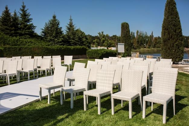 Białe drewniane krzesła na zielonym trawniku. białe fotele dla gości