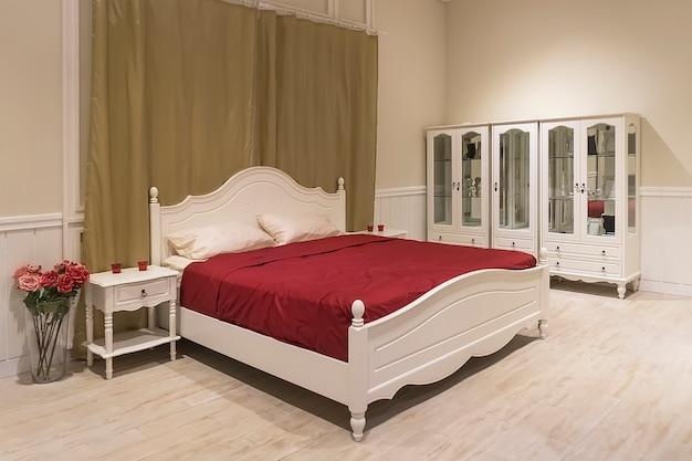Białe drewniane łóżko z ciemnoczerwonym kocem i białymi poduszkami. pokój apartament dla nowożeńców w drogim hotelu. przytulna sypialnia. komoda, antresola, stolik nocny, stolik kawowy