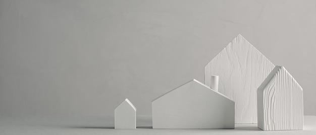 Białe drewniane małe domy z zabawkami na szarym tle minimalistyczny skandynawski wzór dekoracyjny