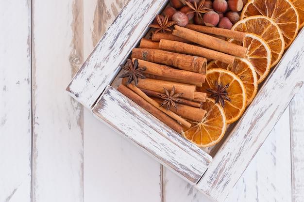 Białe drewniane pudełko z aromatycznymi zimowymi przyprawami - suszone pomarańcze, laski cynamonu, gwiazdki anyżu i orzechy na drewnianym tle z miejscem na kopię