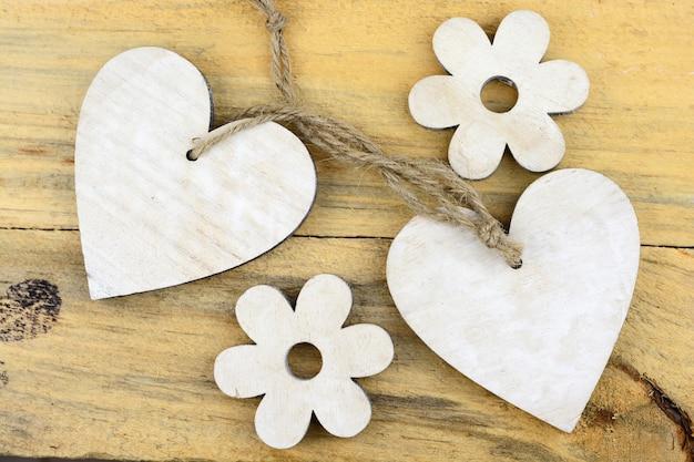 Białe drewniane serca i kwiaty na drewnianej powierzchni