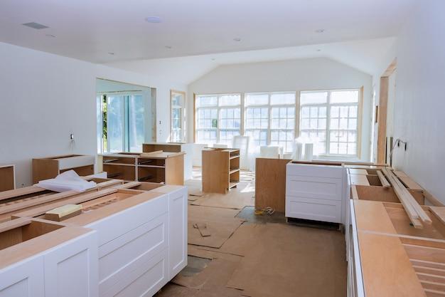 Białe drewniane szafki kuchenne ze współczesną podstawą montażową