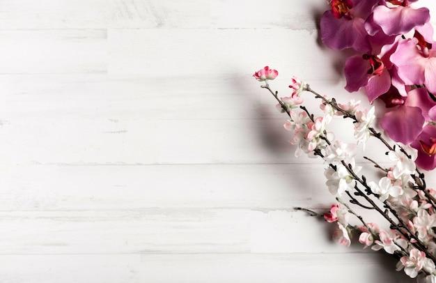 Białe drewniane tła z pięknymi kwiatami