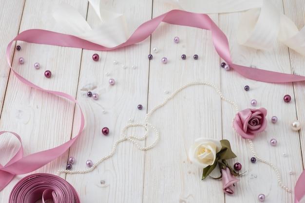 Białe drewniane tła z różowe kwiaty, wstążki i koraliki. styl ślubu