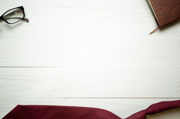 Białe drewniane tło z czerwonym krawatem i okularami. idealne zaplecze biznesowe