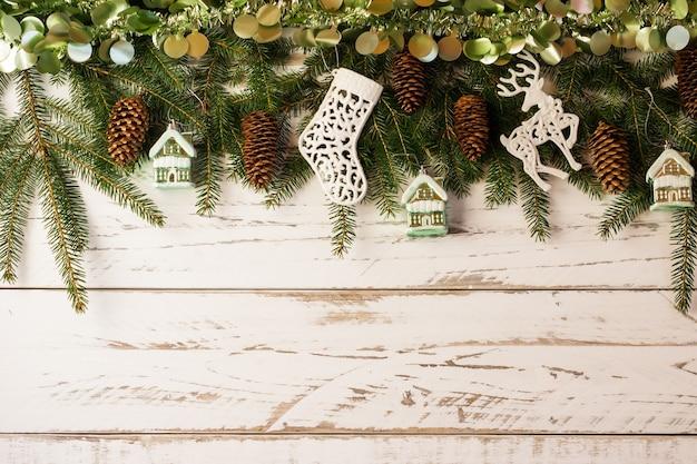 Białe drewniane tło z dużą świąteczną girlandą świerkowych zielonych gałęzi, leśnych szyszek, świątecznych zabawek - domy, skarpety, jelenie. kopiuj specyfikację.