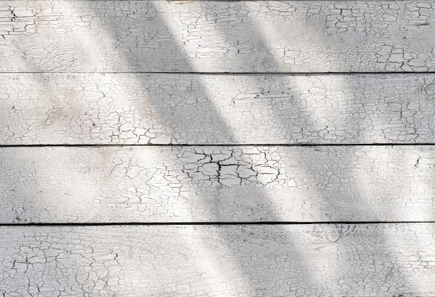 Białe drewniane wytarte deski wyblakłe ze światłem słonecznym, stare lekkie biurko pęknięte farby deska drewno vintage tekstura, promienie słoneczne na rustykalnym stole wzór szorstki nierówny grunge retro łuszcząca się struktura, widok z góry