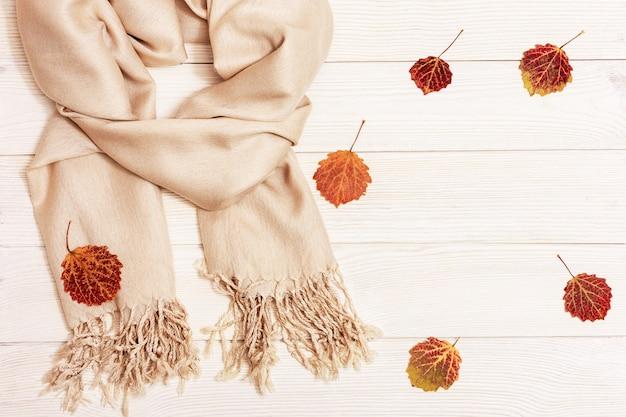 Białe drewno z suchymi czerwonymi liśćmi sezonu jesiennego z drzewa osiki i przytulny szalik tekstylny