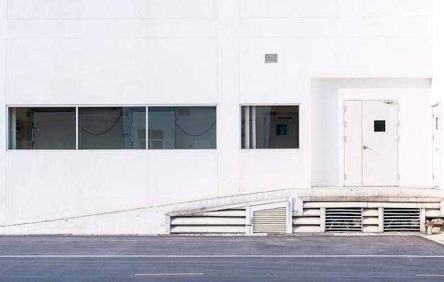 Białe drzwi wejściowe fabryki w parku przemysłowym, widok na zewnętrzną architekturę budynku przemysłowego