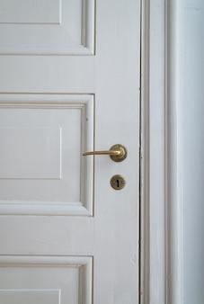 Białe drzwi z klamką