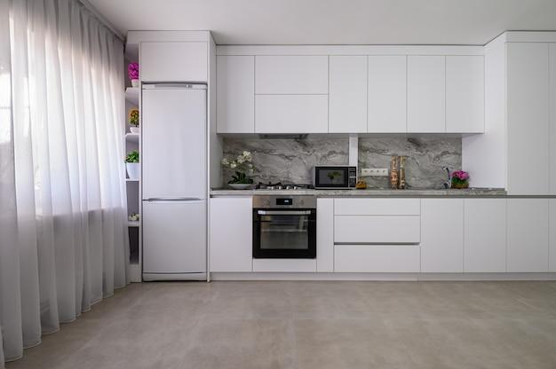 Białe duże nowoczesne wnętrze kuchni