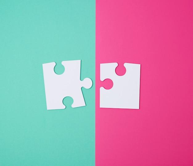 Białe duże puste puzzle na różowo-zielonej