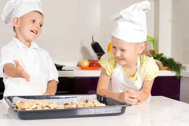 Białe dzieciaki w fartuchu zrobiły pyszną pizzę w kuchni