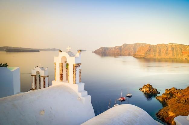 Białe dzwonnice kościelne i kaldera wulkanu z krajobrazem morza egejskiego, piękne szczegóły wyspy santorini, grecja, stonowane
