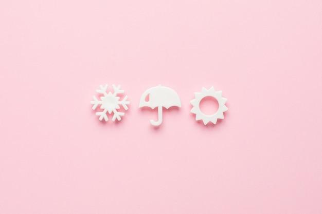 Białe elementy pogodowe w minimalistycznym stylu na różowym, widok z góry.