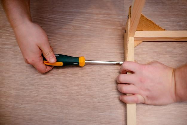 Białe europejskie mężczyzna ręki z śrubokrętem pracuje z drewnem i śrubami.