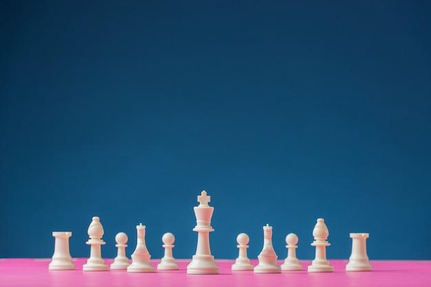 Białe figury szachowe ustawione na różowej szachownicy z figurą króla jako prowadzącą