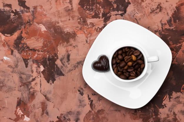 Białe filiżanki do espresso wypełnione ziarnami kawy i czekoladą w kształcie serca. widok z góry, miejsce. tło żywności
