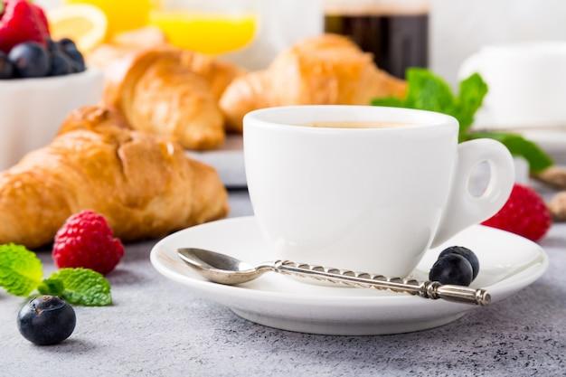 Białe filiżanki kawy i rogaliki