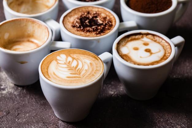 Białe filiżanki z różnych etapów przygotowania cappuccino. koncepcja miłośnika kawy martwa natura