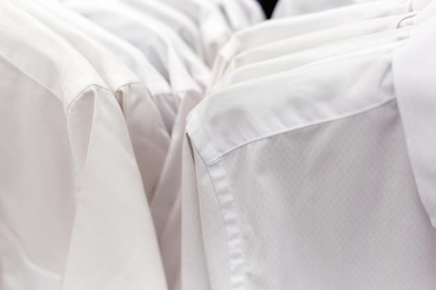 Białe formalne koszule wiszące na wieszaku