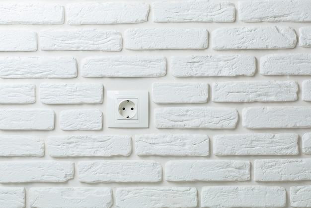 Białe gniazdo na ścianie z cegły.
