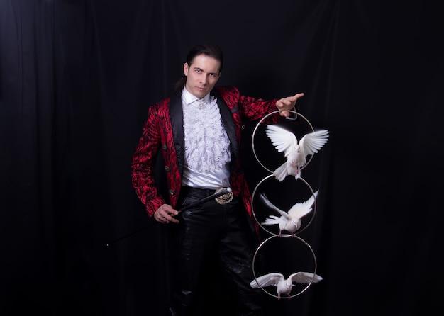 Białe gołębie w obręczy na rękach maga lub przywoływacza