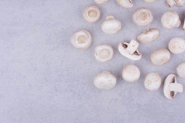 Białe grzyby na białym tle na szarej powierzchni
