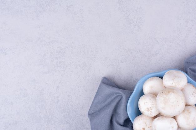 Białe grzyby w niebieskiej misce na ziemi