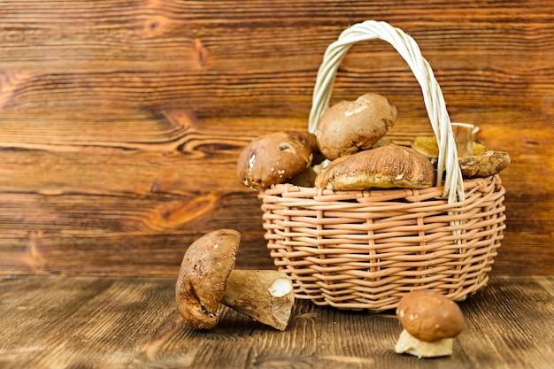 Białe grzyby w rustykalnym wiklinowym koszu. drewniane tło.