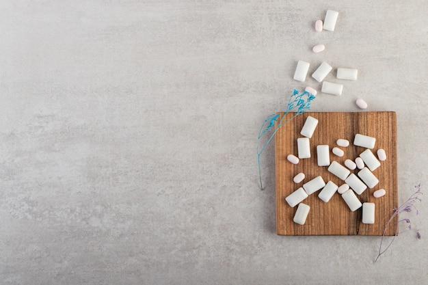 Białe gumy do żucia ustawione na kamiennym stole.