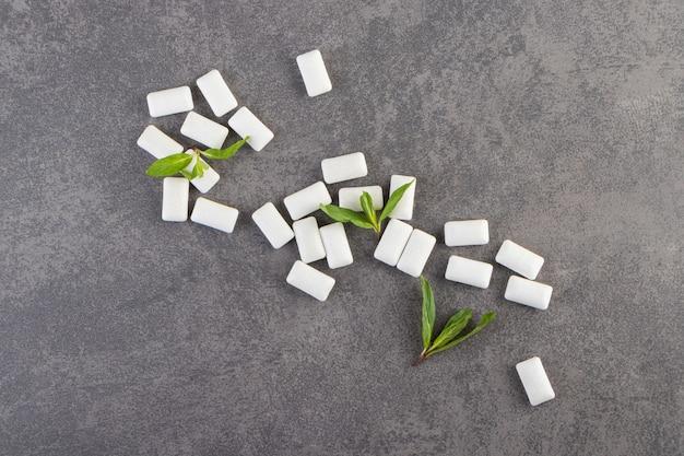 Białe gumy do żucia z listkami mięty ułożone na kamiennym stole.