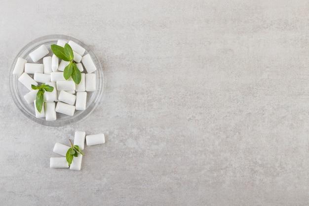 Białe gumy z listkami mięty w szklanej misce.