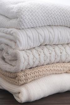 Białe i beżowe swetry są ułożone w stos. różne wzory dzianin. tło jesień lub zima.