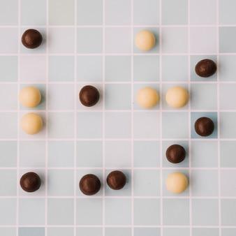 Białe i ciemne czekoladowe kulki na tle szachownicą