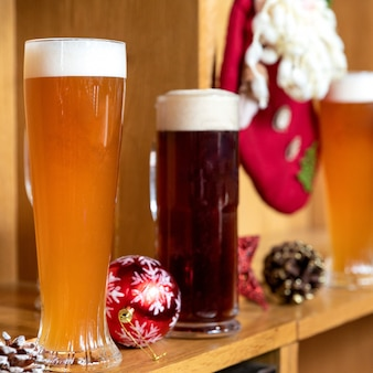 Białe i ciemne szklanki do piwa, kubki ze świątecznymi świątecznymi zabawkami, dekoracje, upominki