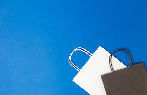 Białe i czarne papierowe torby z uchwytami na niebieskiej ścianie