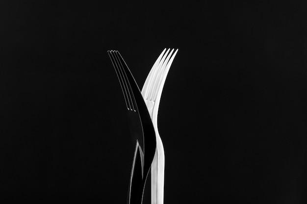 Białe i czarne plastikowe widelce na czarnym tle. widelce stoją na boki, opierając się o siebie i tworzą rodzaj x.