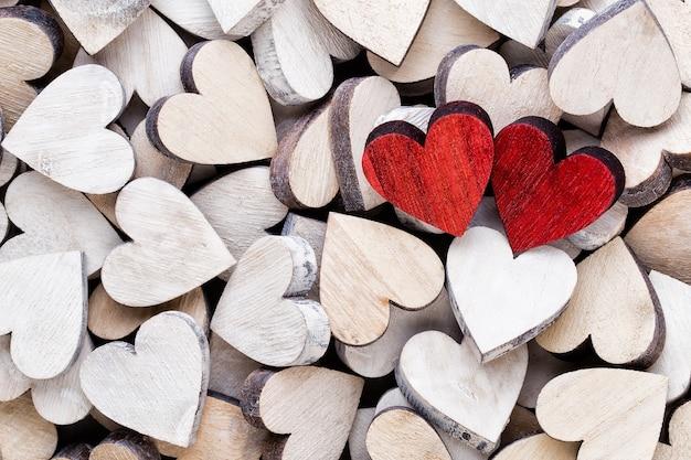 Białe i czerwone serca, tło z drewnianymi sercami.