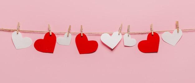 Białe i czerwone serce szpilka na linie na na białym tle różowym tle, koncepcja miłości i valentine