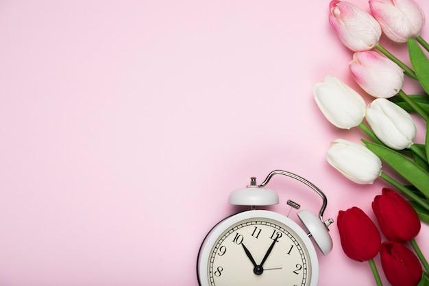 Białe i czerwone tulipany obok zegara z miejsca na kopię